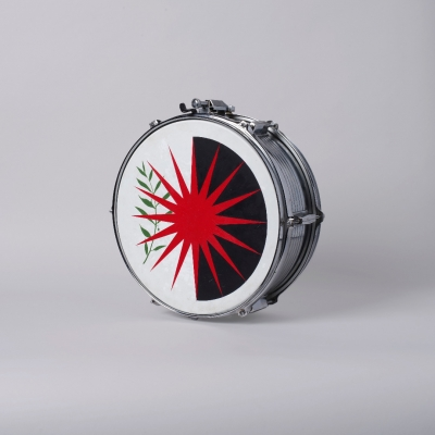 """Jasmina Cibic, """"All that power melts into noise (Bonaventura_Proposal n.761)"""", 2020, acrylic on snare drum, courtesy of the artist: A photographic reproduction of a snare drum decorated with an emblem. The image of the proposed League of Nations flag was made with acrylic paint. The predominant colors of the composition are red, black, green and white."""
