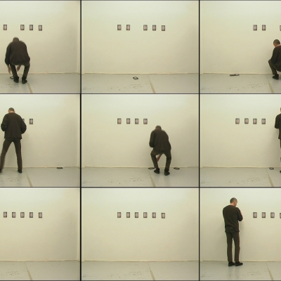 """Igor Krenz, """"Things"""", 2003-2007, video, collection of Muzeum Sztuki, Łódź: A man dressed in black is hanging small frames with pictures on the wall. They are falling off."""