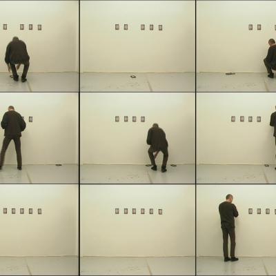 """Igor Krenz, """"Rzeczy"""", 2003-2007, wideo, z kolekcji Muzeum Sztuki w Łodzi: Mężczyzna ubrany na czarno zawiesza małe ramki, które spadają."""