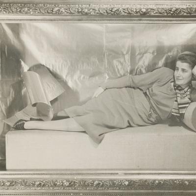 """Aleksander Krzywobłocki, """"Portret pani Adler (na kanapie)"""", 1932 r., fotografia czarno-biała, z kolekcji Muzeum Sztuki w Łodzi: Na czarno-białej fotografii znajduje się postać przedstawiająca młodą kobietę w leżącej pozie. Oprawę fotografii stanowi ozdobna rama zamykająca kompozycję, którą wzbogacają liczne misterne sztukaterie."""