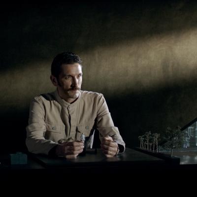 """Jasmina Cibic, """"Dar"""", 2021, jednokanałowe wideo HD, stereo , dzięki uprzejmości artystki: W półmroku, przy biurku siedzi mężczyzna ubrany w beżowy uniform. Trzyma on małe figurki ludzi, po prawej stronie znajduje się makieta ze szklanym trójkątem i drzewami."""
