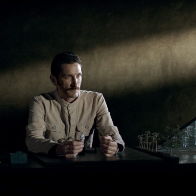 """Jasmina Cibic, """"The Gift"""", 2021, single channel HD video stereo, courtesy of the artist: In the dark room, a man dressed in a beige uniform is sitting at a desk. He is holding small figures of people, on the right side there is a model with a glass triangle and trees."""