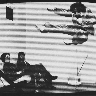 """ZygmuntRytka, """"Bluff"""", 1978 r., fotografia czarno-biała, z kolekcji Muzeum Sztuki w Łodzi : Czarno-biała fotografia ukazująca mężczyznę w eleganckim garniturze, ćwiczącego karate. W lewym dolnym rogu usytuowane są dwie kobiety, w pozycji siedzącej, uważnie przypatrujące się mężczyźnie"""