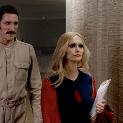 """Jasmina Cibic, """"The Gift"""", 2021, single channel HD video stereo, courtesy of the artist: A man dressed in a beige uniform is following a woman with blonde hair who is holding files."""