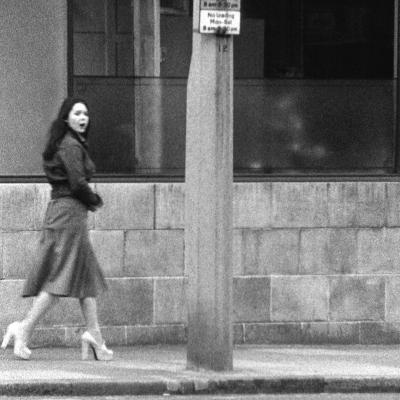 """John Smith, """"Dziewczyna żująca gumę / The Girl Chewing Gum"""", 1976 film, 11'46'', z kolekcji Muzeum Sztuki w Łodzi: Kobieta, elegancko ubrana, idzie ulicą i żuje gumę."""