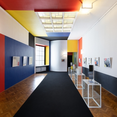 """Władysław Strzemiński, """"Neoplastic Room"""", present view, 2020, photo: Anna Zagrodzka, collection of Muzeum Sztuki, Łódź: The view of the Neoplastic Room. The walls are white, black, red, blue and yellow. On the left and right, there are paintings on the wall. On the right, there are sculptures on pedestals."""