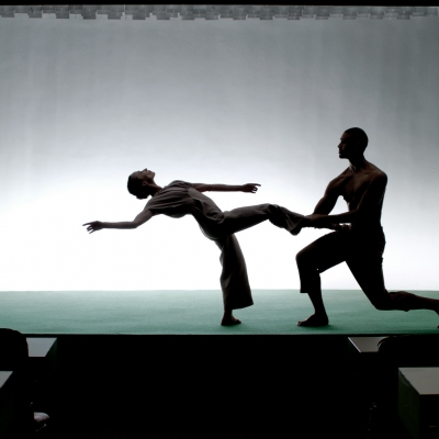"""Jasmina Cibic, """"The Gift"""", 2021, single channel HD video stereo, courtesy of the artist: A man and a woman are on the stage performing a choreography against an illuminated wall. The man is on one knee and holding the woman by the leg."""