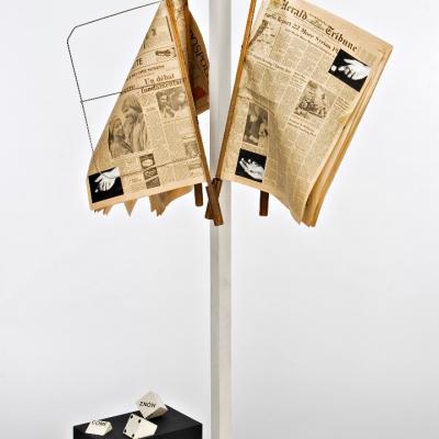 """Peter Downsbrough, """"Bez tytułu"""", 1982, drewno, metal, gazeta, fotografia, z kolekcji Muzeum Sztuki w Łodzi: Na wieszaku zawieszone są pożółkłe gazety. Na dole znajdują się kostki do gry z napisami"""