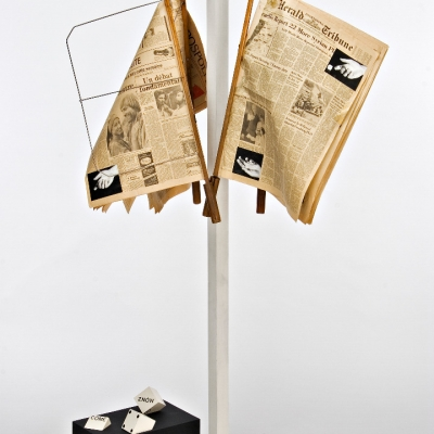 """Peter Downsbrough, """"Untitled"""", 1982, wood, metal, newspaper, photography, paints, collection of Muzeum Sztuki, Łódź: Old, yellow newspapers are hanging on a hanger. Below them, there are dices with writings"""