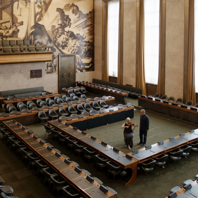 """Jasmina Cibic, """"The Gift"""", 2021, single channel HD video stereo, courtesy of the artist: In the middle of the large conference hall, which is empty, there is an elderly woman playing the violin. An older man is standing next to her. The photo is taken from above."""