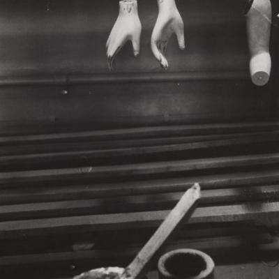 """Jan Kosidowski, """"Wytwórnia manekinów"""", 1966-1967 r., fotografia czarno-biała, z kolekcji Muzeum Sztuki w Łodzi : Czarno-biała fotografia prezentująca warsztat pracy. W górnej części zdjęcia znajdują się wiszące niekompletne części ciała porcelanowych manekinów, dół zdjęcia zagospodarowany jest przez narzędzia malarskie."""