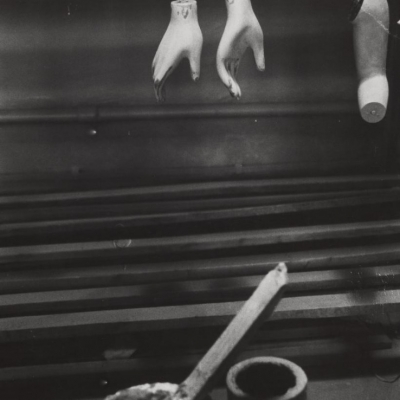 """Jan Kosidowski, """"Mannequin factory"""", 1966-1967, black-and-white photograph, from the collection of Muzeum Sztuki in Łódź : A black-and-white photo presents the workshop. In the upper part of the photo, there are hanging incomplete body parts of porcelain mannequins, the bottom of the photo is decorated with painting tools."""