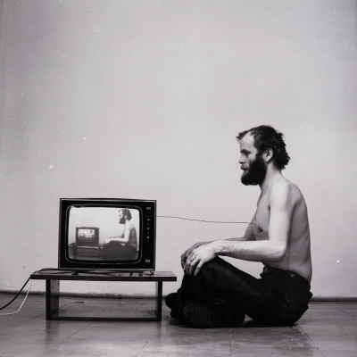 """Paweł Kwiek, """"Video and breath. The channel of information"""", 1978/2016, black-and-white photograph, collection of Muzeum Sztuki, Łódź: A black-and-white photograph shows a man facing the TV. The photograph documents aperformance in which the artist coupled his breath with the TV screen."""