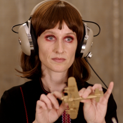 """Jasmina Cibic, """"The Gift"""", 2021, single channel HD video stereo, courtesy of the artist: The woman is wearing headphones over her ears and holding a small airplane figurine in her hands."""
