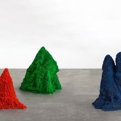 """Agnieszka Kurant, """"A.A.I. (Artificial Artificial Intelligence)"""", 2015, termite mounds built by colonies of living termites out of colored sand, gold and crystals, collaboration: dr Paul Bardunias, dr Leah Kelly, private collections: The reproduction shows three termite mounds composed of colored sand, gold and crystals. The objects located close to each other are characterized by saturated colors, from the left: green, red and blue. The irregular form of the mounds emphasizes their organic nature. The background is a white wall presenting the mounds clearly."""
