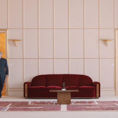 """Jasmina Cibic, """"The Gift"""", 2021, single channel HD video stereo, courtesy of the artist: An older man in a navy blue uniform is entering the white room from the left. On the right, there is a locked door. In the center of the frame, there is a red sofa, a table and a carpet."""