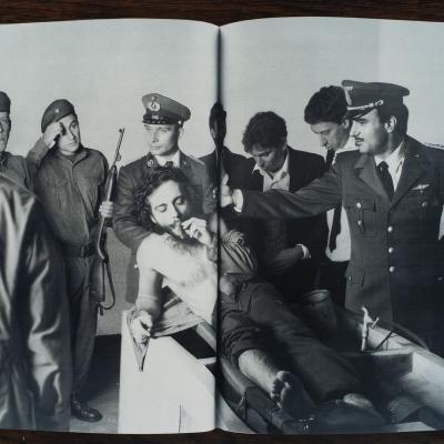 """Zbigniew Libera, """"Che. Następny kadr, z cyklu Pozytywy"""", 2003 r., fotografia, z kolekcji Muzeum Sztuki w Łodzi : Czarno-biała fotografia prezentująca zainscenizowaną sytuację. Na zdjęciu przestawiony jest mężczyzna w pozycji leżącej, palący cygaro w obecności 8 mężczyzn. Pięciu z nich ma na sobie mundury."""
