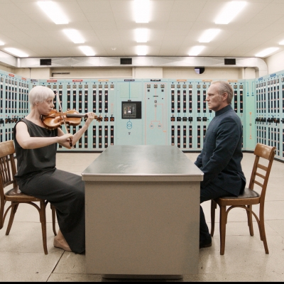"""Jasmina Cibic, """"The Gift"""", 2021, single channel HD video stereo, courtesy of the artist: An older man and an older woman are sitting, facing each other, in a room that resembles an electricity room of the building. They are surrounded by various devices. The woman is playing the violin."""