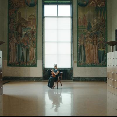 """Jasmina Cibic, """"Dar"""", 2021, jednokanałowe wideo HD, stereo , dzięki uprzejmości artystki: Starsza kobieta trzyma skrzypce. Znajduje się ona w ogromnym korytarzu, po lewej i prawej stronie znajdują się drewniane szafki. Nad nią znajdują się dwa duże obrazy."""