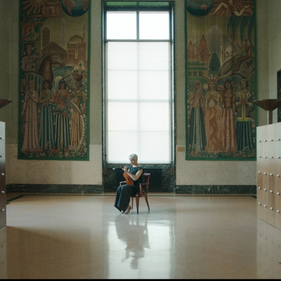 """Jasmina Cibic, """"The Gift"""", 2021, single channel HD video stereo, courtesy of the artist: An elderly woman is holding a violin. She is in a huge corridor with wooden cabinets on the left and right side. There are two large paintings above her."""