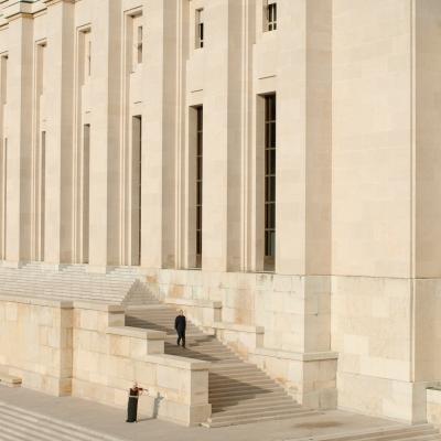 """Jasmina Cibic, """"Dar"""", 2021, jednokanałowe wideo HD, stereo , dzięki uprzejmości artystki: Kadr pokazuje budynek z zewnątrz, wykonany on jest z białego kamienia. Starszy mężczyzna schodzi po schodach, kobieta gra na skrzypcach przed budynkiem."""