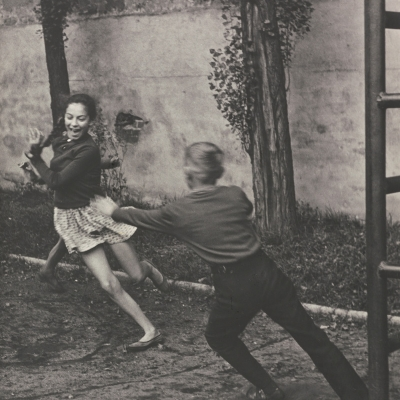"""Bogdan Dziworski, """"Untitled (Chasing children)"""", black-and-white photograph, from the collection of Muzeum Sztuki in Łódź: Two children, a boy and a girl, are playing tag on the playground."""