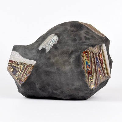 """Agnieszka Kurant, """"Post-Fordite"""", 2020, fossilized automotive paint, epoxy resin, iron, powdered stone, collaboration and photo: Krzysztof Smaga: The reproduction shows the fossil produced by the artist, created by combining a dozen fordites from bankrupt factories from various parts of the world. The composition is dominated by earthy colors with slight accents on the truncated edges of the object."""
