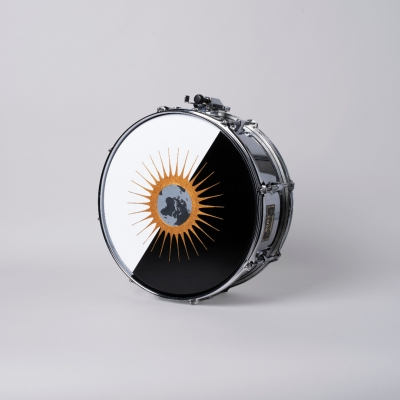 """Jasmina Cibic, """"All that power melts into noise (Spravedlnosťou k pravde. Pravdou k ludstvu_Proposal n.72)"""", 2020, acrylic on snare drum, courtesy of the artist: A photographic reproduction of a snare drum decorated with an emblem. The image of the proposed League of Nations flag was made with acrylic paint. The predominant colors of the composition are black, white, gold and shades of gray."""