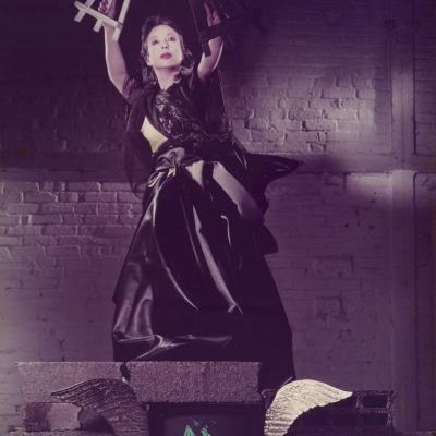 """ORLAN, """"Vierge noire with a white and black easel"""" [Czarna dziewica z białą i czarną sztalugą], 1983, fotografia barwna, z kolekcji Muzeum Sztuki w Łodzi : Kobieta ubrana na czarno trzyma nad głową dwie sztalugi w teatralnym geście."""