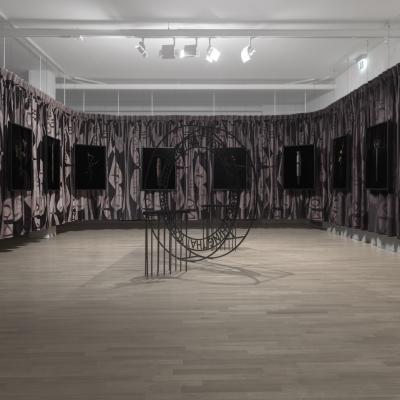 """Jasmina Cibic, """"Rozkosz wydatków"""", widok wystawy, Museum of Contemporary Art Metelkova, fot: Matevž Paternoster, dzięki uprzejmości artystki: Fotografia przedstawia widok wystawy. Kadr obejmuje serię 10 obiektów nasyconych symboliką. W centralnej części kompozycji zdjęcia znajduje się obszerna  instalacja."""