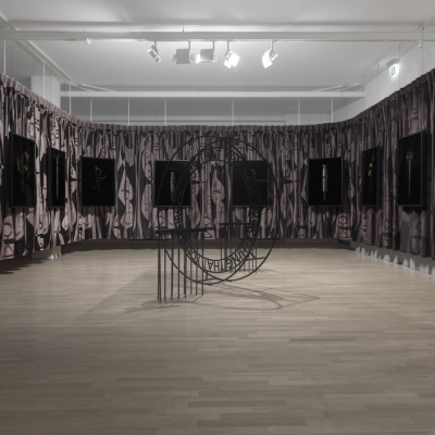 """Jasmina Cibic, """"The Foundation of Endeavour"""", exhibition view, Museum of Contemporary Art Metelkova, photo: Matevž Paternoster, courtesy of the artist: The photo shows the view of the exhibition. The frame includes a series of 10 objects saturated with symbolism. There is an installation in the central part of the composition of the photo."""