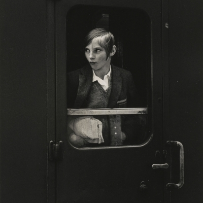 """Ewa Rubinstein, """"Girl on Train"""", 1969, black-and-white photograph, from the collection of Muzeum Sztuki in Łódź: A short-haired woman in a suit, in half-figure shot , is sitting on a train and looking out the window."""