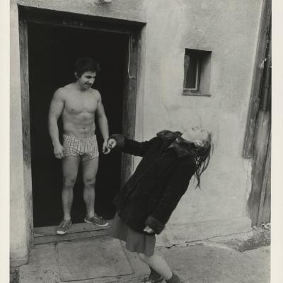 """Jindřich Štreit, """"Bez tytułu"""", 1980 r., fotografia czarno-biała, z kolekcji Muzeum Sztuki w Łodzi: Czarno-biała fotografia przedstawia mężczyznę stojącego w progu domu w samej bieliźnie. Obok niego znajduje się kobieta, która, śmiejąc się, odchyla się do tyłu."""