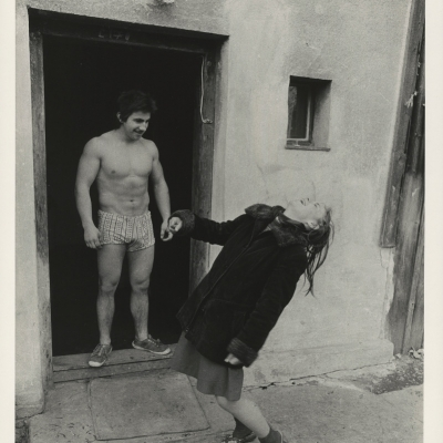 """Jindřich Štreit, """"Untitled"""", 1980, black-and-white photograph, from the collection of Muzeum Sztuki in Łódź: On the doorstep, a muscular man is standing in boxer shorts and boots. Next to him, there is a laughing, clothed woman, leaning back."""