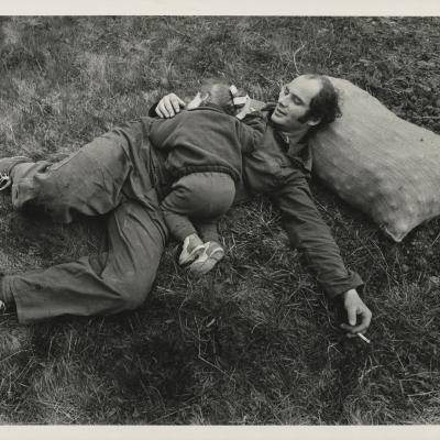 """Jindřich Štreit, """"Bez tytułu"""", 1980 r., fotografia czarno-biała, z kolekcji Muzeum Sztuki w Łodzi: Czarno-biała fotografia przedstawia mężczyznę leżącego na trawie. Głowę opiera na worku z ziemniakami. Na jego brzuchu leży mała dziewczynka."""