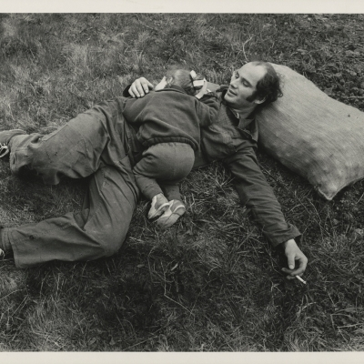 """Jindřich Štreit, """"Untitled"""", 1980, black-and-white photograph, from the collection of Muzeum Sztuki in Łódź: A man is lying on the grass with his head resting on a sack of potatoes with a cigarette in his hand. A few-years old child is hugging him."""