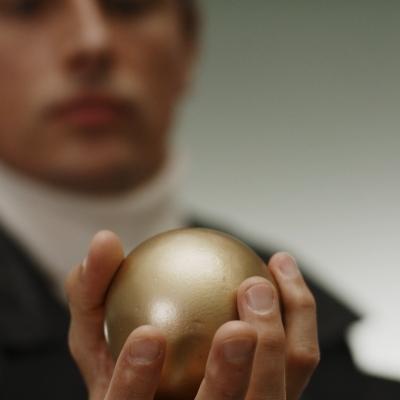 """Jasmina Cibic, """"Dar"""", 2021, zrzut ekranu, dzięki uprzejmości artystki: Na pierwszym planie znajduje się złota kula, którą trzyma w dłoni mężczyzna."""