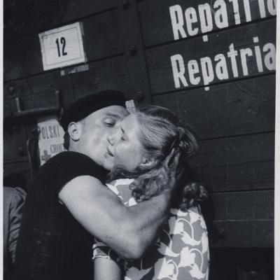 """Julia Pirotte, """"Pożegnanie dworzec w Lille"""", 1945 r., fotografia czarno-biała, z kolekcji Muzeum Sztuki w Łodzi: Czarno-biała fotografia przedstawia mężczyznę całującego kobietę. W tle widać drewniany wagon z napisem"""