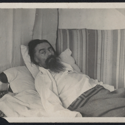 """Unknown author, """"Kazimierz Malewicz, lying in bed"""", 1934-35, black-and-white photograph, from the collection of Muzeum Sztuki in Łódź: An elderly man with beard and a white shirt is lying on the bed covered with a blanket."""