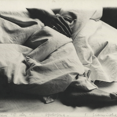"""Teresa Gierzyńska, """"Calm"""" from the series """"About her"""", 1980, black-and-white photograph, from the collection of Muzeum Sztuki in Łódź: The body of the person lying underneath is sticking out below under a piece of white, crumpled linen. At the top, there is a hand, at the bottom, there is a foot."""