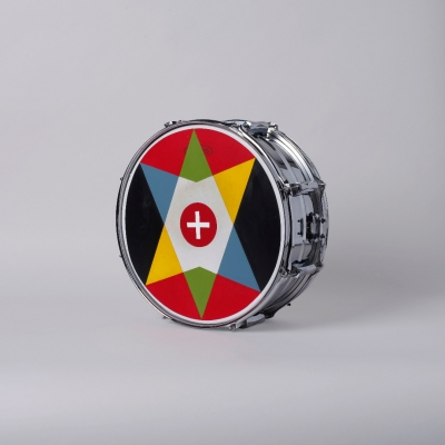 """Jasmina Cibic, """"All that power melts into noise (Un pour Tous_Proposal n.720 B)"""", 2020, acrylic on snare drum, courtesy of the artist: A photographic reproduction of a snare drum decorated with an emblem. The image of the proposed League of Nations flag was made with acrylic paint. The predominant colors of the composition are red, black, green, white, yellow and blue."""