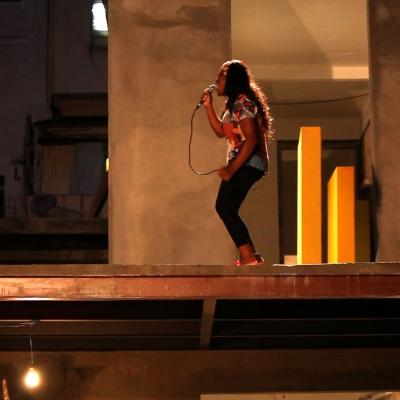 """Wendelien van Oldenborgh, """"Bete & Deise"""", 2019, film work in architectural setting, 41 min, produced by """"If I Can't Dance, I Don't Want To Be Part Of Your Revolution"""" (Amsterdam), courtesy of the artist.: A young woman performs on stage in the evening. She is speaking or singing into the microphone."""
