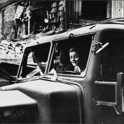 """EugeniuszHaneman, """"W zdobytej ciężarówce"""", 1944/1980, fotografia, z kolekcji Muzeum Sztuki w Łodzi: Fotografia czarno-biała przedstawiająca pojazd, w którym siedzi radosne dziecko oraz osoba dorosła. Całość w anturażu zdegradowanej rzeczywistości."""