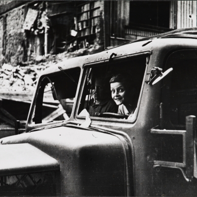 """Eugeniusz Haneman, """"In a trophy truck"""", 1944/1980, black-and-white photograph, from the collection of Muzeum Sztuki in Łódź: A black-and-white photograph shows a vehicle in which a joyful child and an adult sit. They are surrounded by degraded reality."""