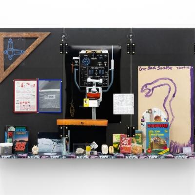 """Michael Stevenson, """"Shield Affordance Extension 1.1 Działalność pozapojazdowa"""", 2020, instalacja, dzięki uprzejmości artysty, Fine Arts, Sydney, oraz Michael Lett Gallery, Auckland: Poziome ujęcie instalacji wiszącej na białej ścianie. Czarna tablica z kolorową półką przy dolnej krawędzi. Obiekt przepełniony kolorowymi przedmiotami takimi jak książki, komiksy, rysunki czy przybory geometryczne."""