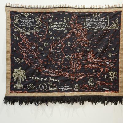 """Cian Dayrit, """"Poruszamy się wśrod duchów"""", 2020, haft na tkaninie (współpraca: Henry Caceres), widok ekspozycji """"We Move Amongst Ghosts"""", kurator: Kayu Lucie Fontaine, 2020, dzięki uprzejmości artysty i NOME, Berlin: Poziome ujęcie tkaniny rozciągniętej na białej ścianie. Ciemno brązowy materiał wykończony beżowym pasem z czarnymi piórami na dole. Na materiale linearnie zaznaczona mapa wysp z licznymi podpisami i symbolami."""
