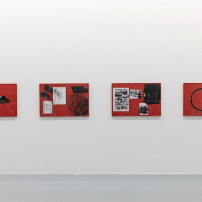 """Céline Condorelli, """"Cotton / Rubber"""", 2017, installation view, FRAC Lorraine (France), photograph by Fred Dott, courtesy of the artist.: The photo shows four screen printing compositions. Two-color prints on red paper are embedded on a white wall. The most dynamic compositions bring together works that are inside. The artworks on the outer sides are characterized by the central arrangement of the blocks."""
