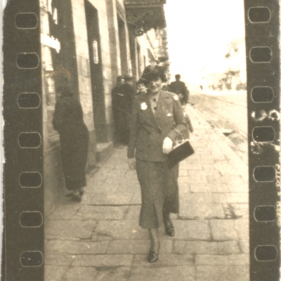"""Unknown author, """"Photographs from the Łódź Ghetto"""", ca. 1942, black-and-white photograph, from the collection of Muzeum Sztuki in Łódź: A black-and-white photograph shows a woman walking confidently towards the author of the photo. The background consists of pedestrians gathered around the tenement house."""