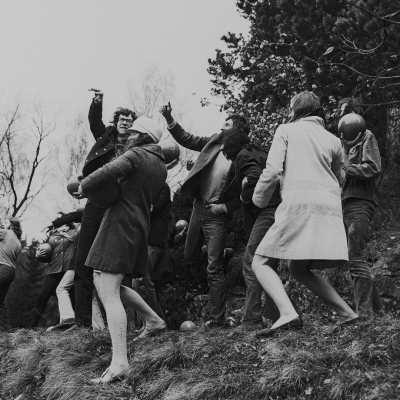 """Zorka Ságlová, """"Documentation of the action titled: Throwing balls into Lake Bořín in Průhonice"""", 1969, black and white photography, collection of Muzeum Sztuki, Łódź: Black-and-white photograph. Women and men dressed in coats are throwing balls into the lake."""