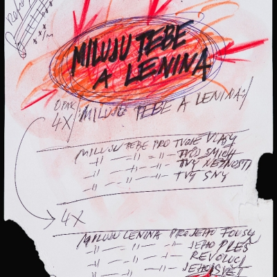 """Milan Knížák, """"Partytura zespołu Aktual [Miluju tebe a Lenina]"""", 1967, długopis, tusz, flamaster, pastel, karton, z kolekcji Muzeum Sztuki w Łodzi: Na białej kartce zapisane są różne notatki. U góry zakreślony jest czerwony okrąg ze strzełkami."""